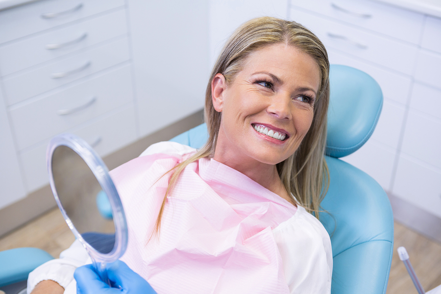 Smiling woman looking away while holding mirror at dental clinic