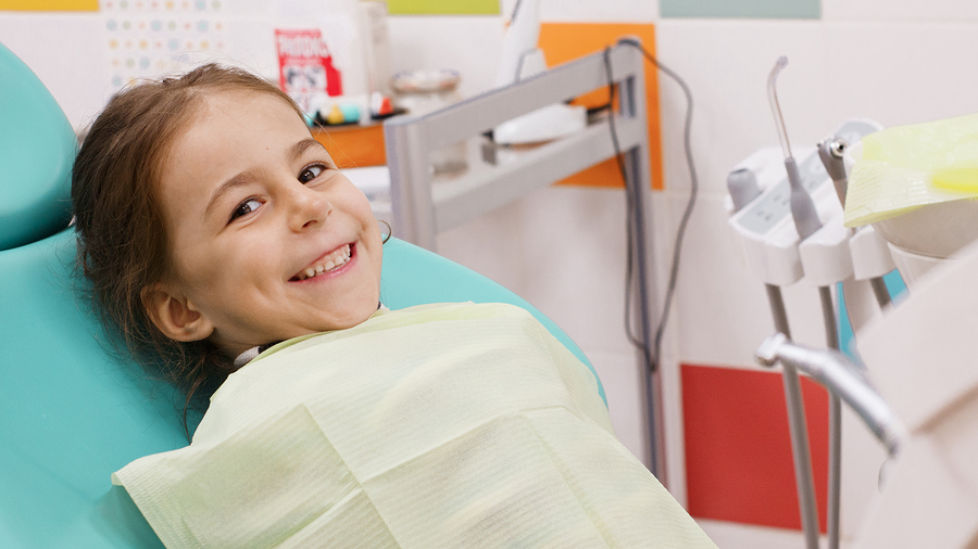 Happy child in a dentist's chair after dental treatment