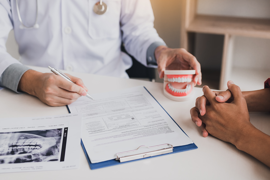 Asian male dentist hand holding pen writing patient history list on note pad.