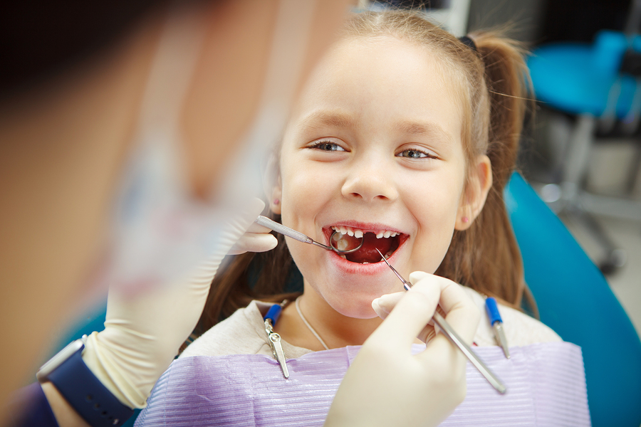 Cute child sits at dentist chair with smile while doctor in rubber gloves examines mouth with instrumets. Kid not scared and feels comfortable at medical procedure.