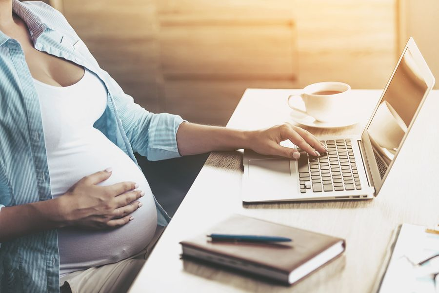 A young pregnant woman in front on a laptop