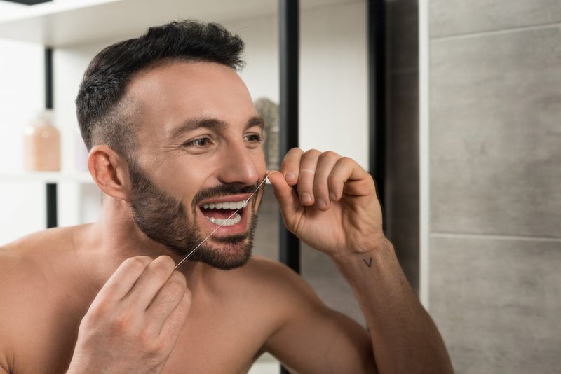bearded shirtless man looking at mirror while using dental floss in bathroom