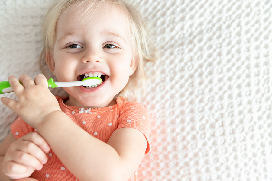 Cute Happy Baby Brushing Teeth and Smiling. Copy Space